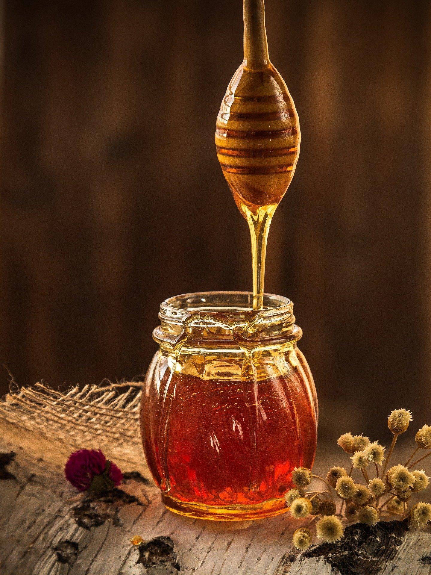 Bâton de miel coulant sur un pot de miel